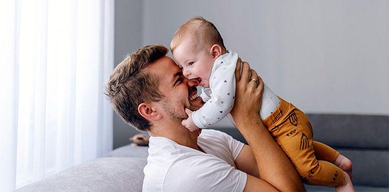 Homme heureux qui porte un bébé dans les bras