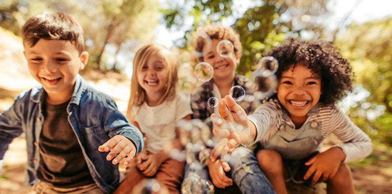 4 enfants qui s'amusent et rient ensemble en plein air