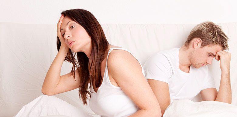 Couple assis sur un lit, se tourne le dos et se tiennet la tête. Ils semblent préoccupés