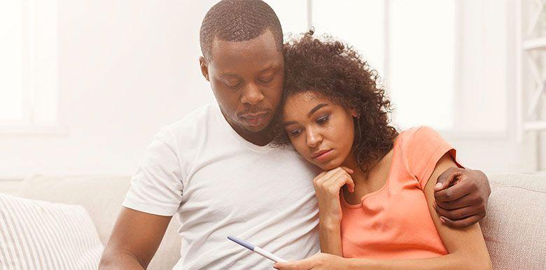 Couple enlacé sur un canapé qui semble déçu. La femme tient un test de grossesse dans sa main
